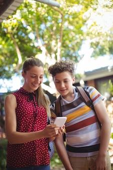 Tevreden klasgenoten die mobiele telefoon gebruiken