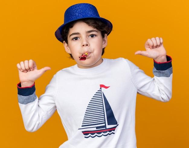 Tevreden kleine jongen met een blauwe feestmuts die een feestfluitje blaast, wijst naar zichzelf