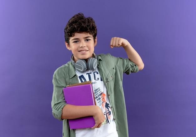 Tevreden kleine schooljongen die een koptelefoon draagt die boeken houdt en een sterk gebaar doet dat op paarse muur wordt geïsoleerd