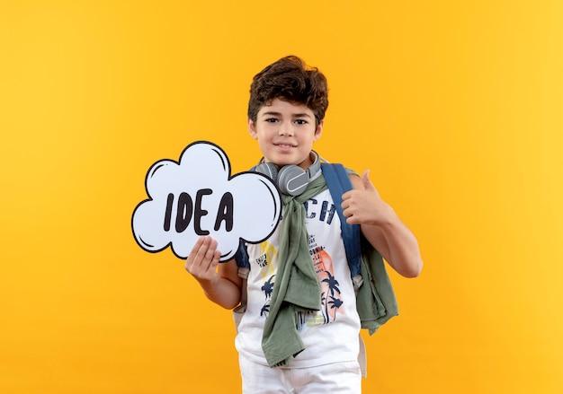 Tevreden kleine schooljongen die rugtas en koptelefoon draagt die ideebel zijn duim houdt omhoog geïsoleerd op gele achtergrond