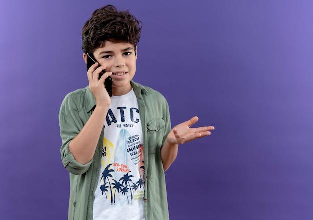 Tevreden kleine schooljongen spreekt aan de telefoon en spreidt zijn hand