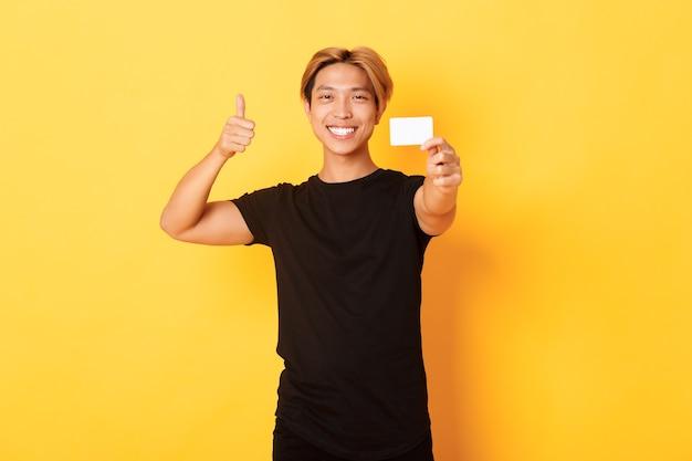 Tevreden knappe aziatische kerel die tevreden glimlacht en creditcard, thumbs-up in goedkeuring toont, die zich gele muur bevindt