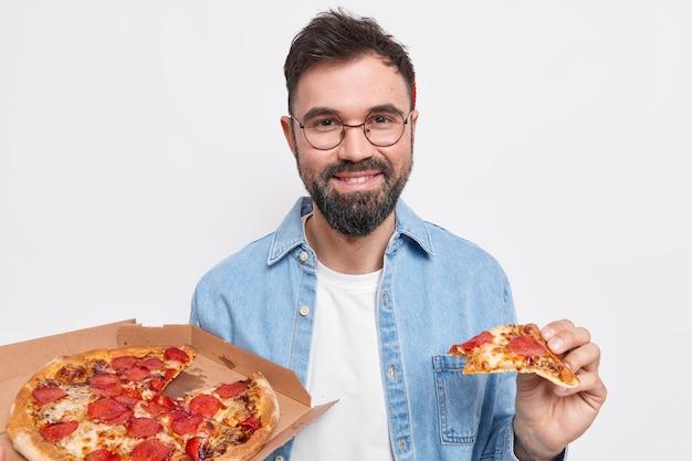 Tevreden knappe bebaarde man eet heerlijke pizza voor het avondeten, heeft honger, draagt een ronde bril en een shirt eet junkfood