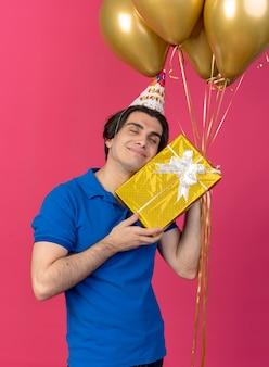 Tevreden knappe blanke man met verjaardagspet houdt heliumballonnen en geschenkdoos vast
