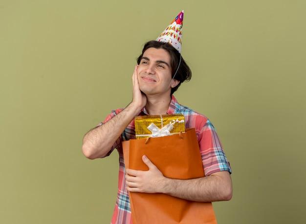 Tevreden knappe blanke man met verjaardagspet legt hand op gezicht en houdt geschenkdoos in papieren boodschappentas