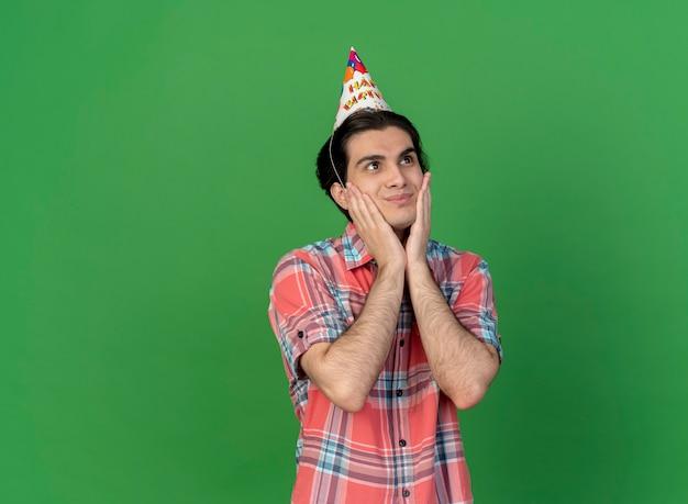 Tevreden knappe blanke man met verjaardagspet legt handen op het gezicht en kijkt naar de zijkant