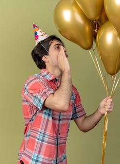 Tevreden knappe blanke man met verjaardagspet staat zijwaarts met de hand dicht bij de mond en kijkt naar heliumballonnen