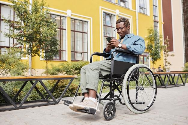 Tevreden knappe jonge zwarte man met handicap zittend in een rolstoel en surfen op internet op smartphone tijdens wandeling