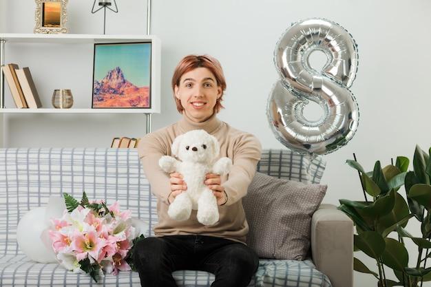 Tevreden knappe kerel op gelukkige vrouwendag die een teddybeer vasthoudt die op de bank in de woonkamer zit