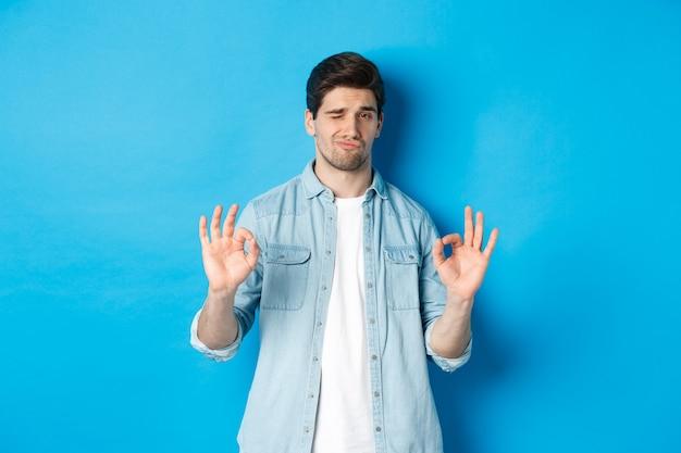 Tevreden knappe man die a-ok tekenen toont en er tevreden uitziet, iets goeds goedkeurt, staande tegen een blauwe achtergrond.