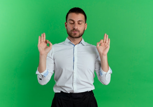 Tevreden knappe man doet alsof hij mediteert met gesloten ogen geïsoleerd op groene muur