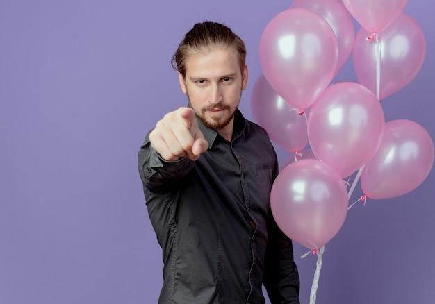 Tevreden knappe man houdt helium ballonnen en punten geïsoleerd op paarse muur