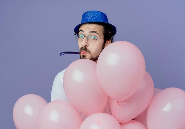 Tevreden knappe man met bril en blauwe hoed achter op ballonnen en fluitje blazen