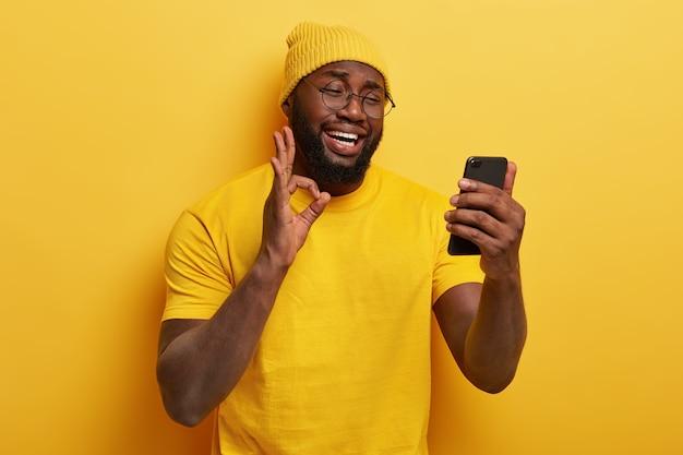 Tevreden knappe man met bril poseren met zijn telefoon