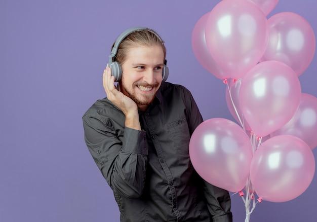 Tevreden knappe man op koptelefoon houdt helium ballonnen kijken kant geïsoleerd op paarse muur
