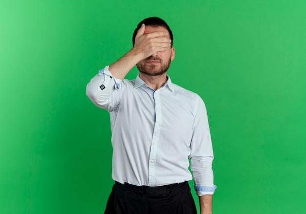 Tevreden knappe man sluit ogen met hand geïsoleerd op groene muur