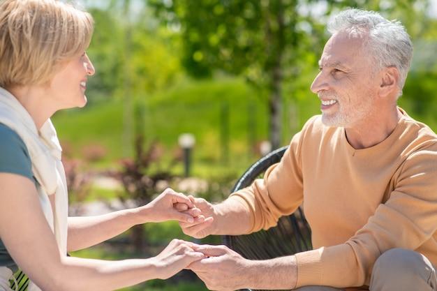 Tevreden knappe volwassen grijsharige blanke man en zijn lachende blonde vrouwelijke echtgenoot hand in hand buiten