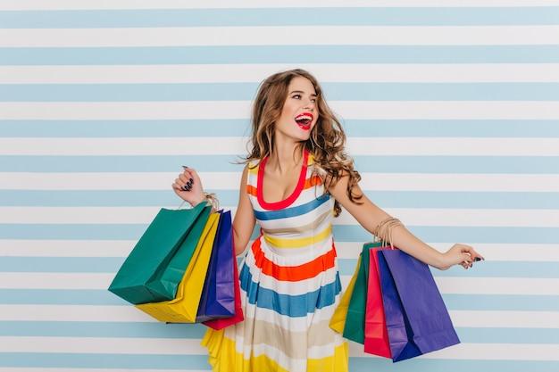 Tevreden krullende vrouw die van verkoop geniet. portret van prachtig meisje dansen na het winkelen.