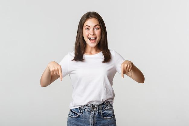 Tevreden lachend brunette meisje wijzende vingers naar beneden, product aanbevelen.