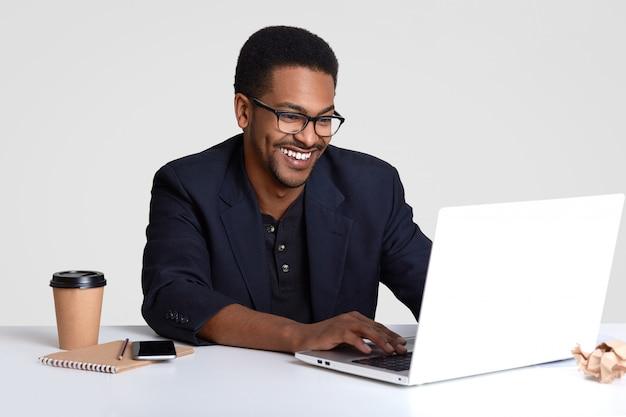 Tevreden lachende man ondernemer met brede glimlach, draagt een bril en zwart pak, toetsenborden informatie op laptopcomputer