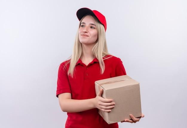 Tevreden levering jong meisje dat rode t-shirt en glb-holdingsdoos draagt op geïsoleerde witte achtergrond
