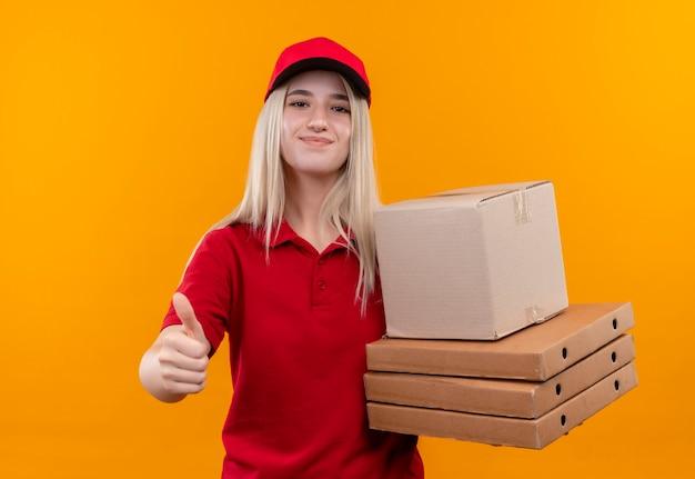 Tevreden levering jong meisje met rode t-shirt en pet met dozen haar duim omhoog op geïsoleerde oranje achtergrond