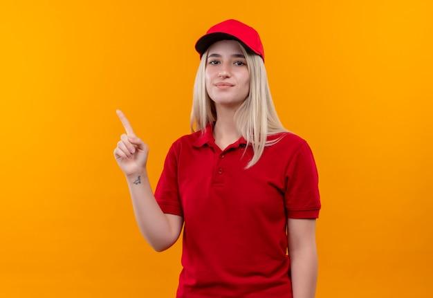 Tevreden levering jong meisje met rode t-shirt en pet wijst naar de zijkant op geïsoleerde oranje achtergrond