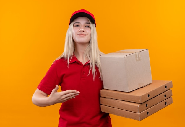 Tevreden levering jong meisje met rode t-shirt en pet wijst naar doos op haar hand op geïsoleerde oranje achtergrond