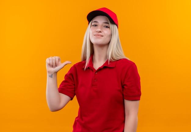 Tevreden levering jong meisje met rode t-shirt en pet wijst naar zichzelf op geïsoleerde oranje achtergrond