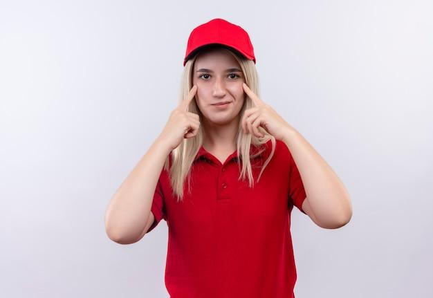 Tevreden levering jong meisje met rood t-shirt en pet legde haar vingers op de ogen op geïsoleerde witte achtergrond