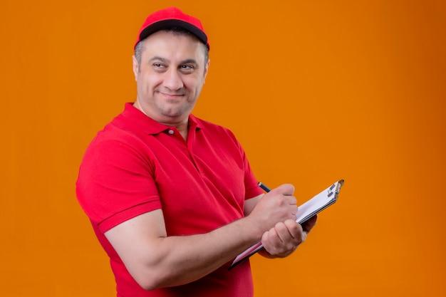 Tevreden leveringsmens die rood uniform draagt en een pet met klembord houdt iets schrijft dat opzij kijkt met een glimlach op het gezicht dat zich over oranje achtergrond bevindt