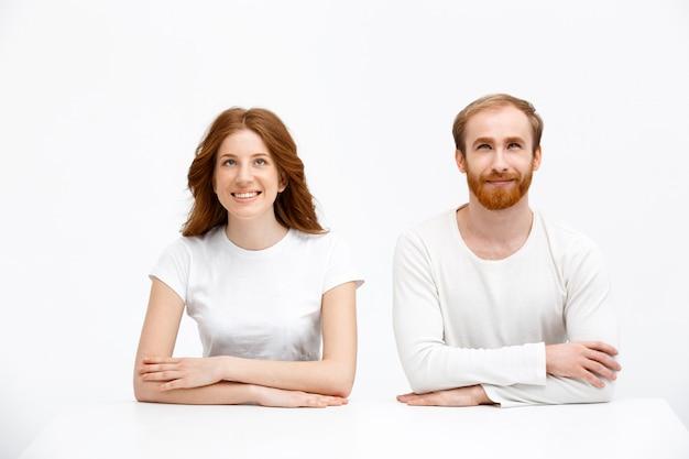 Tevreden man en vrouw, beide roodharigen kijken op