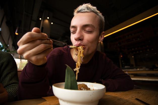 Tevreden man geniet van eten in het restaurant