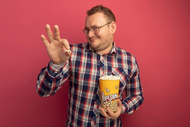 Tevreden man in glazen en geruit overhemd met emmer met popcorn lachend met blij gezicht staande over roze muur