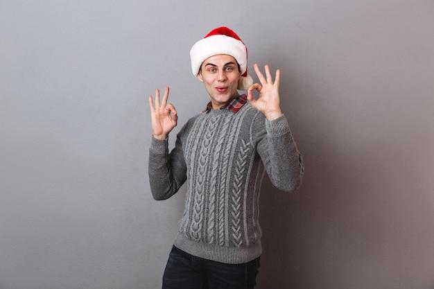 Tevreden man in trui en kerstmuts met ok teken en duim omhoog tijdens het kijken