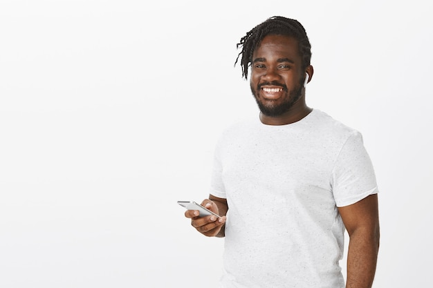 Tevreden man met vlechten poseren tegen de witte muur met zijn telefoon