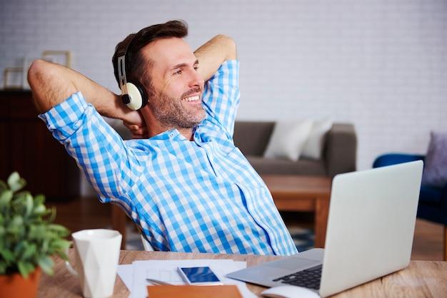Tevreden man rust en luistert naar muziek in zijn kantoor