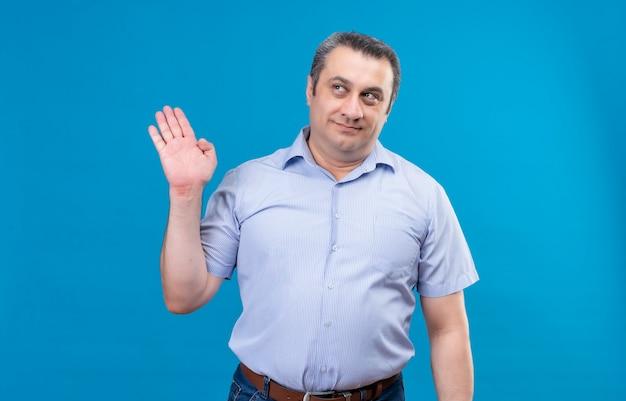 Tevreden man van middelbare leeftijd die blauw gestreept overhemd draagt dat hand op een blauwe achtergrond opheft
