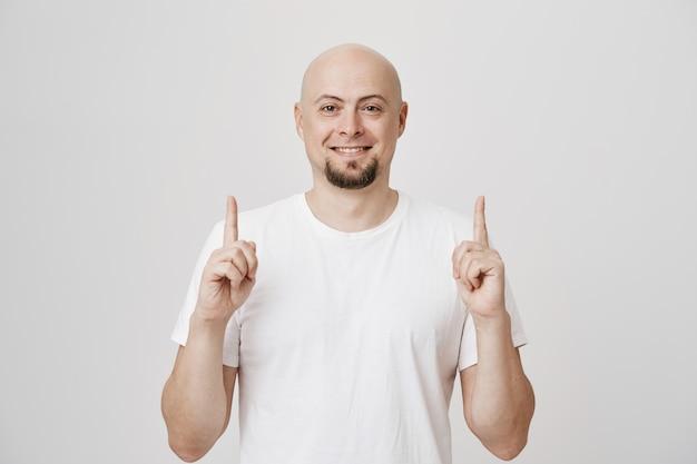 Tevreden man van middelbare leeftijd glimlachend, wijzende vingers omhoog
