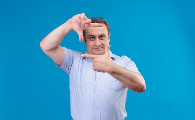 Tevreden man van middelbare leeftijd in blauw gestreept overhemd dat frame met zijn hand op een blauwe ruimte maakt