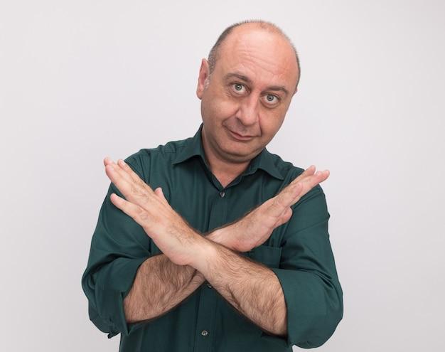 Tevreden man van middelbare leeftijd met een groene t-shirt met gebaar van nee geïsoleerd op een witte muur