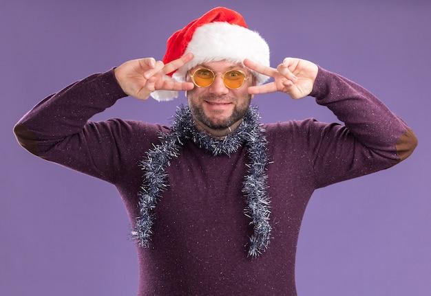 Tevreden man van middelbare leeftijd met kerstmuts en klatergoud slinger rond de nek met bril kijken naar camera met v-teken symbolen