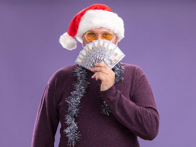 Tevreden man van middelbare leeftijd met kerstmuts en klatergoud slinger rond de nek met een bril die geld van achteren houdt geïsoleerd op paarse muur