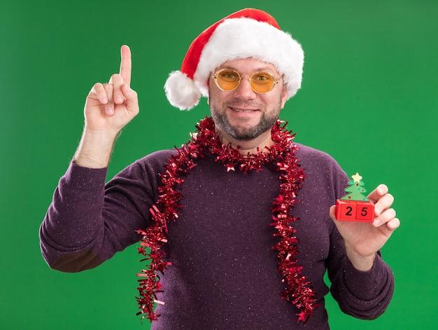 Tevreden man van middelbare leeftijd met kerstmuts en klatergoud slinger rond de nek met een bril met kerstboom speelgoed met datum
