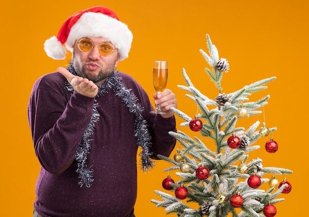 Tevreden man van middelbare leeftijd met kerstmuts en klatergoud slinger rond de nek met glazen staande in de buurt van versierde kerstboom met glas champagne