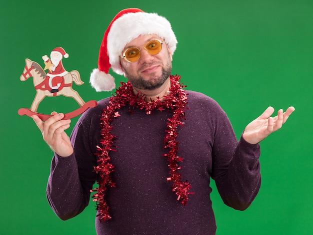 Tevreden man van middelbare leeftijd met kerstmuts en klatergoudslinger rond de nek met een bril die santa op het beeldje van het hobbelpaard houdt