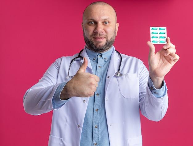 Tevreden mannelijke arts van middelbare leeftijd die een medisch gewaad en een stethoscoop draagt die een pakje medische capsules naar voren toont en naar de voorkant kijkt met duim omhoog geïsoleerd op roze muur