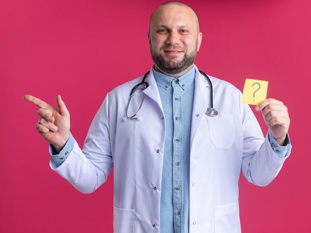 Tevreden mannelijke arts van middelbare leeftijd die een medisch gewaad en een stethoscoop draagt en naar de voorkant kijkt met een vraagteken dat naar de zijkant wijst geïsoleerd op een roze muur