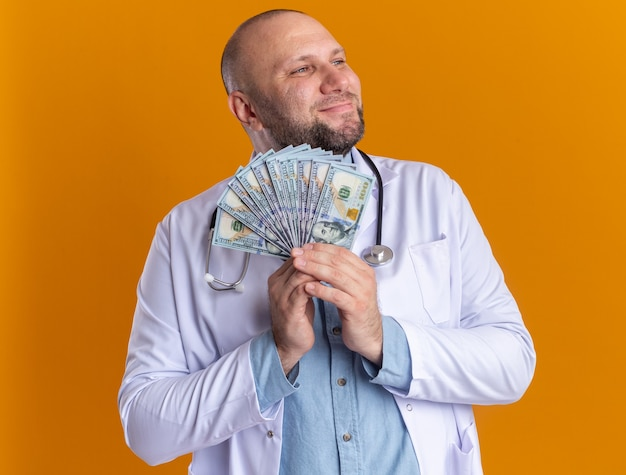 Tevreden mannelijke arts van middelbare leeftijd met een medisch gewaad en een stethoscoop die geld vasthoudt en naar de zijkant kijkt die op een oranje muur is geïsoleerd