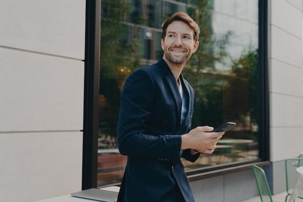 Tevreden mannelijke directeur controleert persoonlijke organizer via smartphone wacht op bericht of telefoontje